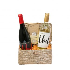 Baúl en mimbre con vinos Little Black Dress Pinot Grigio, Little Black Dress Diva Red y chocolate Lattenero 51% de Slitti